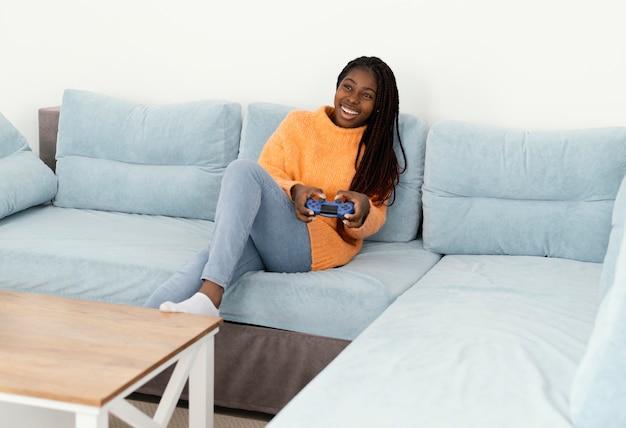 ソファでビデオゲームをしているスマイリーの女の子