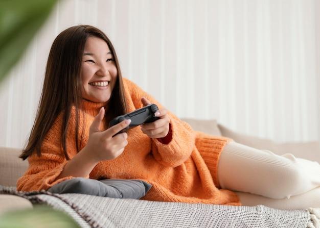 コントローラーでビデオゲームをプレイするスマイリーの女の子