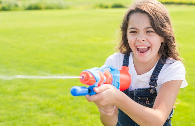 Smiley girl playing with water gun