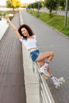 Smiley girl posing with her rollerblades outdoors