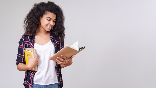 Smiley girl reading with copy-space