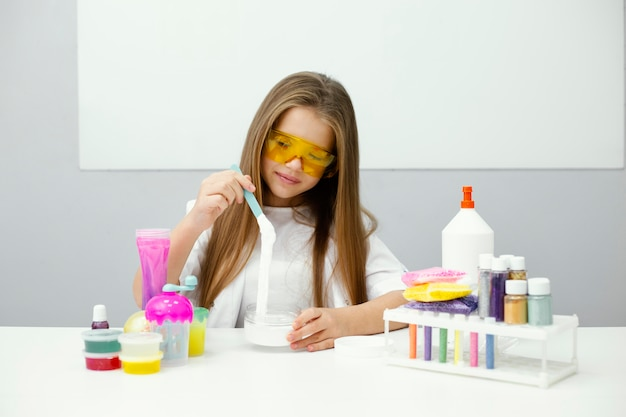 실험실에서 점액을 만드는 웃는 소녀 과학자