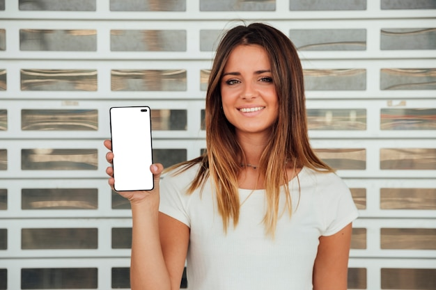Smiley girl showing cellphone with mock-up