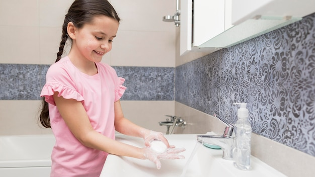 Smiley girl washing her hands side view