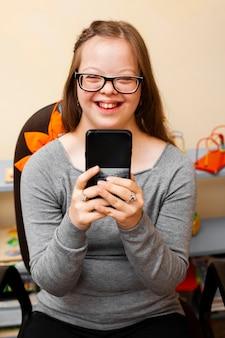 Улыбающаяся девушка с синдромом дауна держит телефон