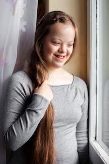 Улыбающаяся девушка с синдромом дауна позирует у окна