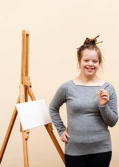 Улыбающаяся девушка с синдромом дауна позирует кистью