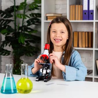 顕微鏡と試験管を持つスマイリーの女の子