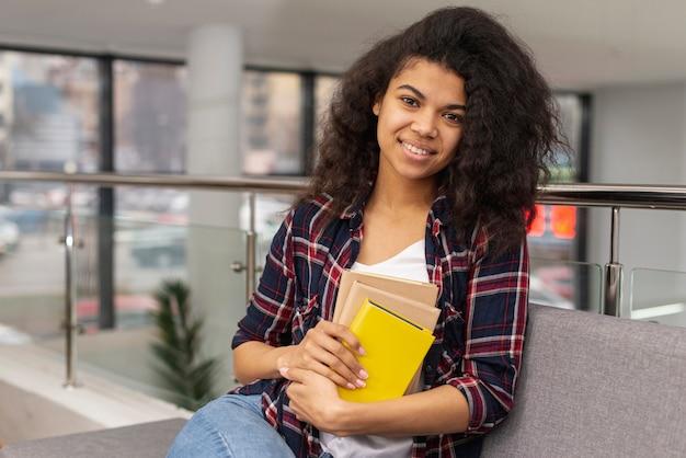 Ragazza sorridente con una pila di libri