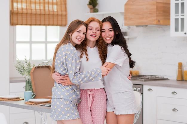 Улыбающиеся подружки дома обнимаются