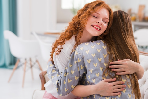 Smiley girlfriends at home hugging
