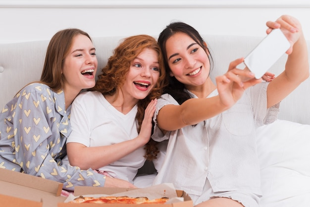 Smiley girlfriends taking selfies