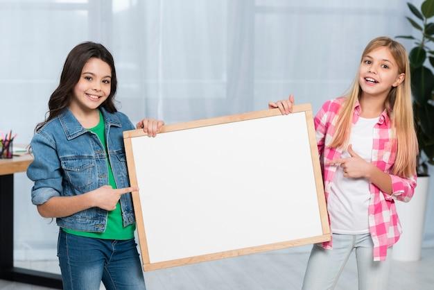 Smiley girls holding frame