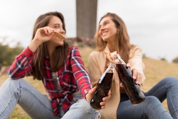 Ragazze di smiley con pizza e soda