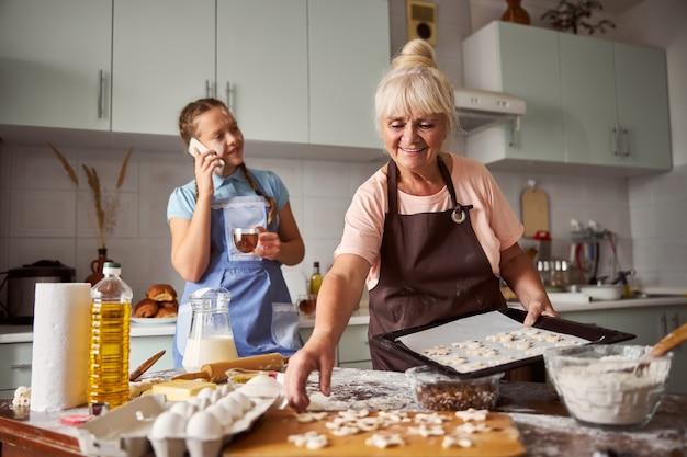 웃는 할머니와 그녀의 손녀가 부엌에서 쿠키를 굽고 있다