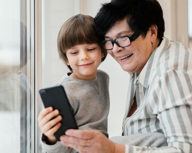 一緒にスマートフォンを見ているスマイリー孫と祖母