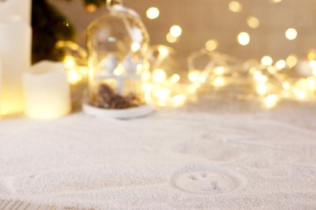 ろうそくのぼやけた花輪の距離で雪に描かれたスマイリーの手..