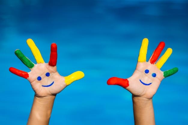 青い水の背景にスマイリーの手夏休みのコンセプト