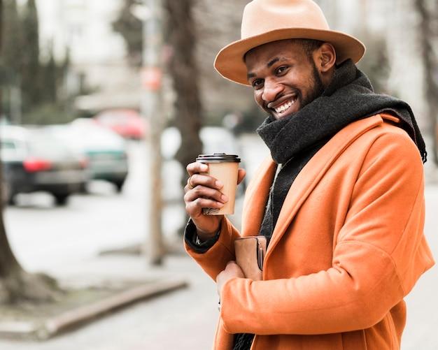 Uomo bello di smiley che tiene una tazza di caffè di carta