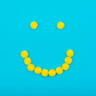 Smiley jelly candies on blue table