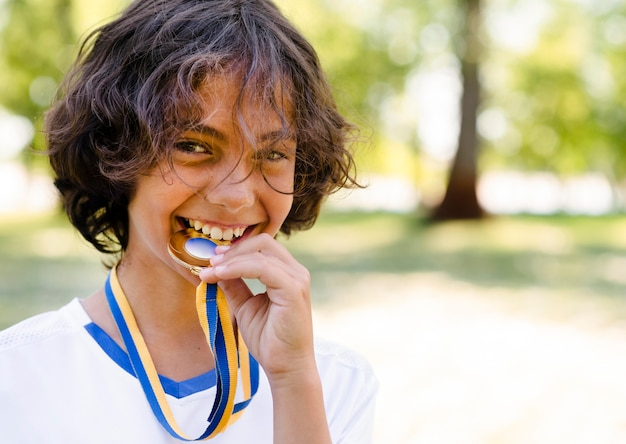Smiley kid biting his medal