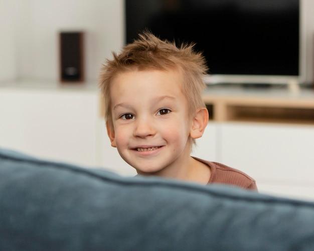 Смайлик малыш позирует на диване