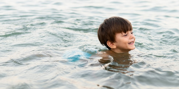 Smiley kid swimming at sea