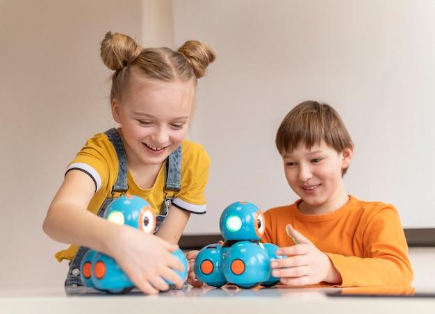 Smiley kids learning at school medium shot Premium Photo