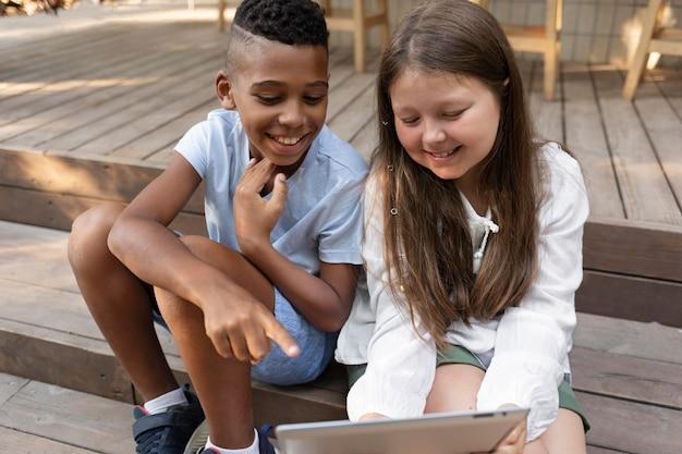 태블릿 미디엄 샷으로 웃는 아이