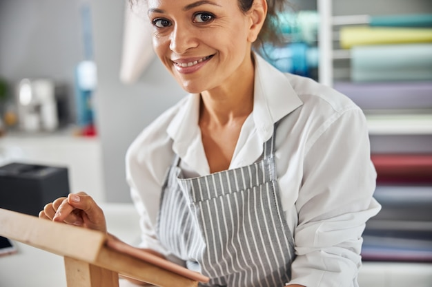 Smiley lady clicking on a tablet while working in shop