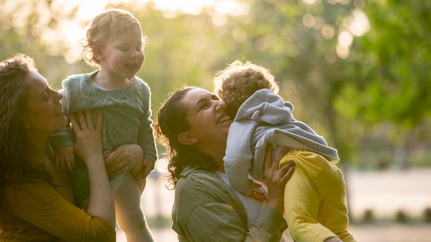 Smiley lgbt mothers outdoors in the park with their children