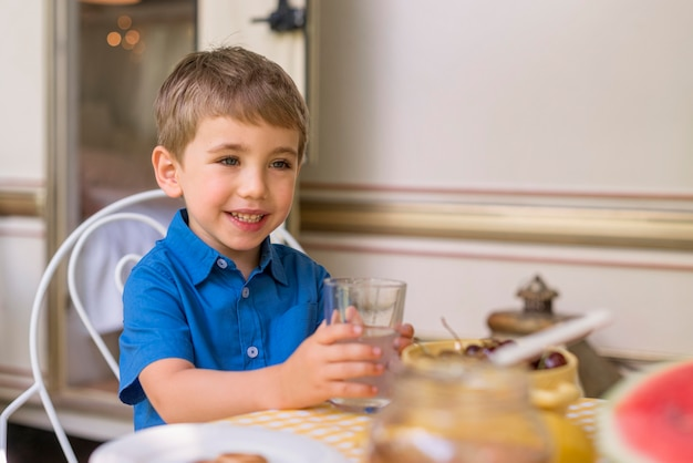 レモネードのガラスを保持しているスマイルの少年