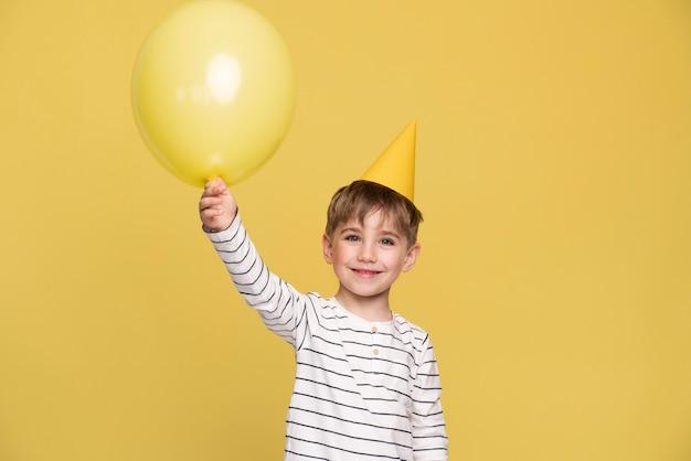 黄色に分離されたスマイリーの小さな男の子