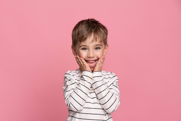 Smiley little boy isolated on pink