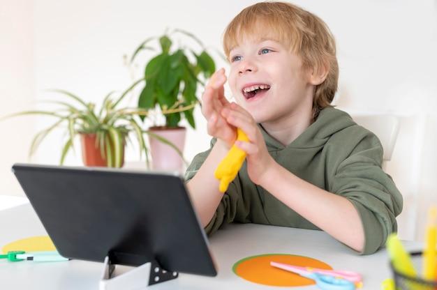 집에서 태블릿을 사용 하여 웃는 어린 소년