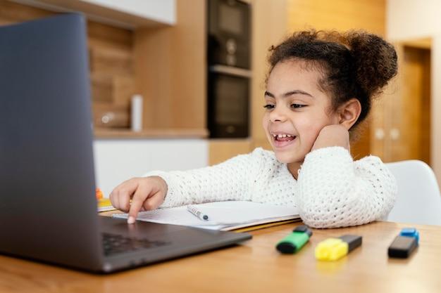 노트북으로 온라인 학교 동안 집에서 웃는 어린 소녀
