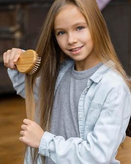 Smiley little girl brushing her hair