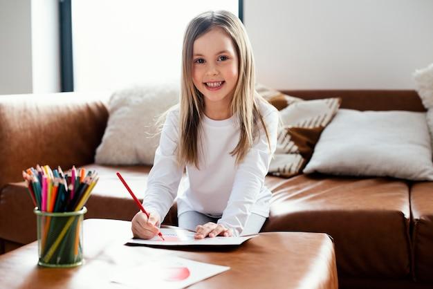 Улыбающаяся маленькая девочка рисует открытку на день отца в качестве сюрприза для своего отца