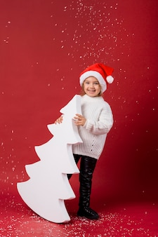 Smiley little girl holding an artificial white tree while snowing
