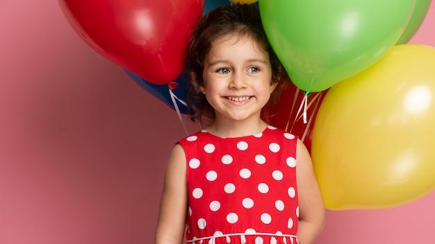 Bambina di smiley in un vestito rosso che celebra il suo compleanno