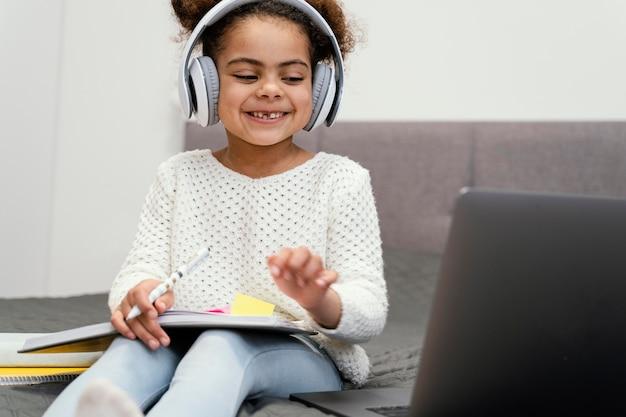 온라인 학교에 노트북을 사용 하여 웃는 어린 소녀