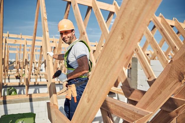 단단한 모자를 쓰고 새 건물에서 드릴 작업을 하는 웃는 남성 건축업자