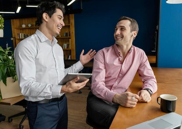 직장에서 대화를 나누는 웃는 남성 동료