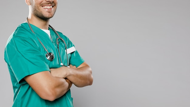 組んだ腕とコピースペースを持つスマイリー男性医師