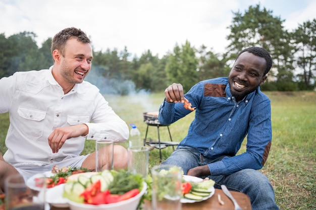 Smiley male friends eating barbecue outdoors