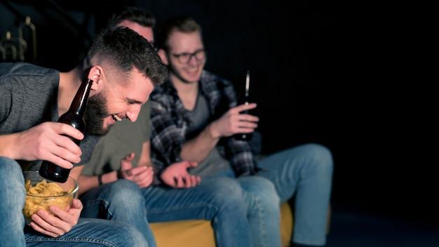 Amici maschi di smiley che guardano insieme lo sport in tv mentre mangiano spuntini e birra