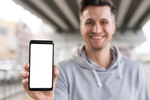 Смайлик мужчина держит мобильный телефон