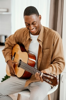 Smiley male musician at home playing guitar