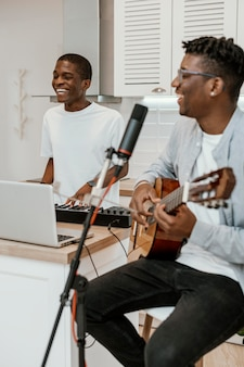 Smiley male musicians at home playing guitar and electric keyboard