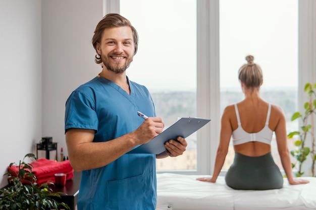 Terapista osteopatico maschio smiley con appunti e paziente femminile presso la clinica